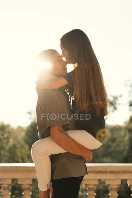 Портрет парня, держащего девушку на руках над мраморным парапетом на заднем плане — стоковое фото