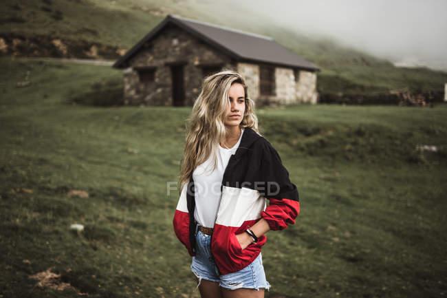 Молодая женщина стоит над старым зданием в горной долине — стоковое фото