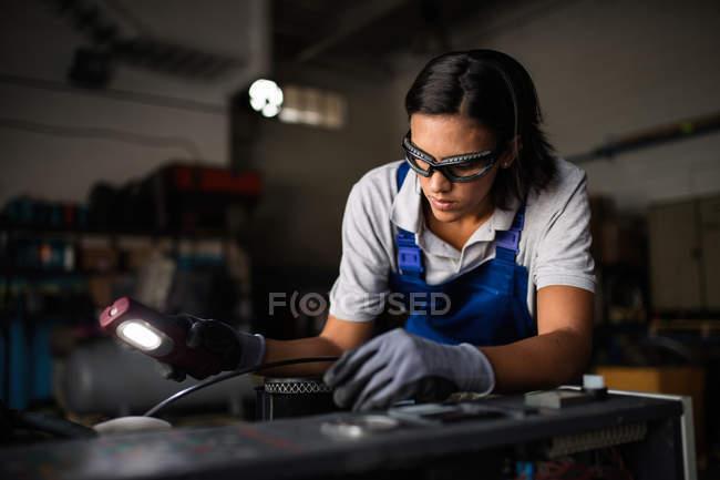 Retrato de mujer mecánico inspección motor del compresor con linterna - foto de stock