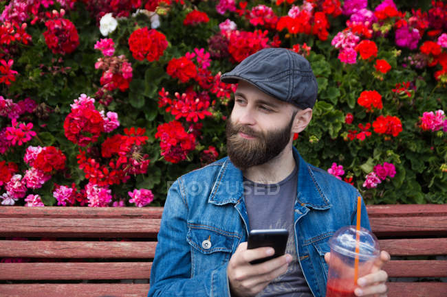 Smiling bearded man sitting on bench beside flowers with smoothie and smartphone in hands and looking away — Stock Photo