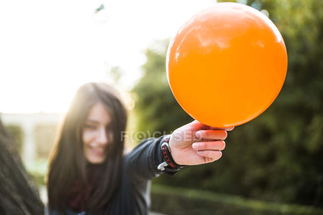 Young brunette holding balloon and in sunlight. — Stock Photo
