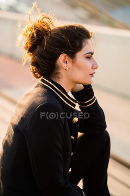 Vue latérale d'une femme posant dans une tenue décontractée et à la recherche. — Photo de stock