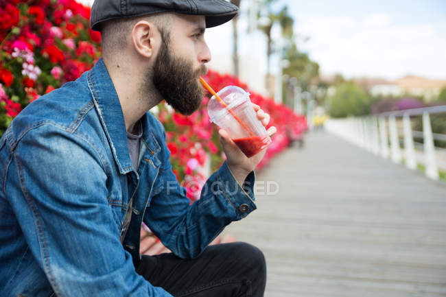 Side view of man drinking smoothie with straw and looking away. — Stock Photo