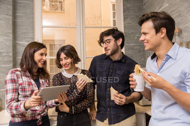 Vier junge Kolleginnen und Kollegen mit Mittagessen und tablet. — Stockfoto