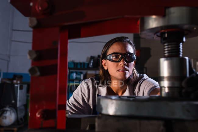 Vista frontal de la mujer prensa de hidráulica de funcionamiento mecánico en garaje - foto de stock