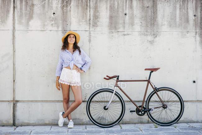 Девушка в шляпе стоит на велосипеде — стоковое фото