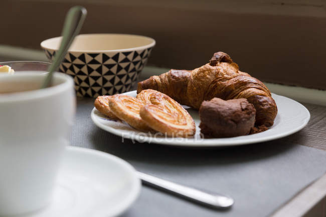 Plate with croissant and cookies on breakfast table — Stock Photo