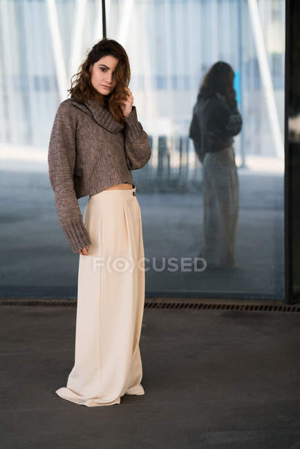 Attractive woman posing in skirt and sweater and looking at camera. — Stock Photo