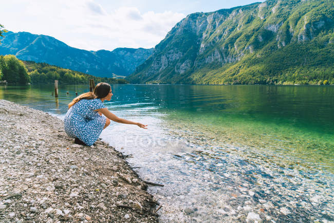 Жінка сидить на озері — стокове фото