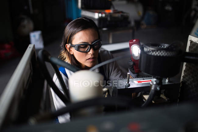 High angle view of female mechanic in protective googles inspecting compressor engine with flashlight — Stock Photo