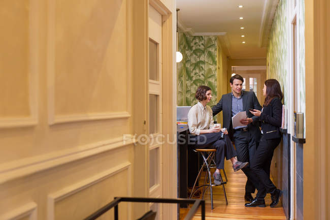 Young employees in suits having discussion in office corridor — Stock Photo