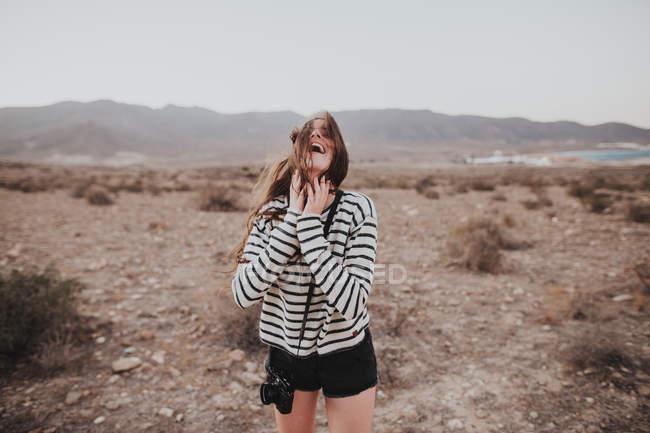 Щасливі брюнетка з цифрової камери, що висить на шиї, сміючись в сільській місцевості — стокове фото