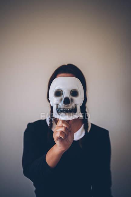 Porträt eines Mädchens im schwarzen Kleid mit Totenkopfmaske vor dem Gesicht — Stockfoto
