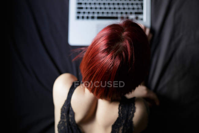 Overhead view of redhead girl browsing laptop on bed — Stock Photo