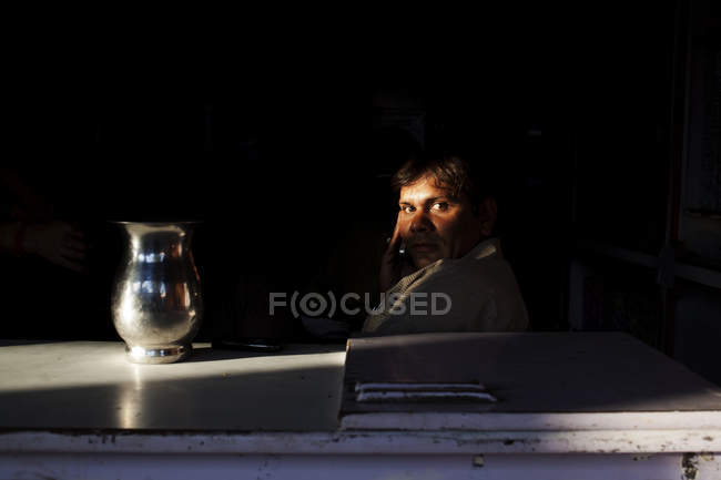 INDIA - 3 October, 2011: Man in suit sitting behind table with pitcher and looking at camera. — Stock Photo