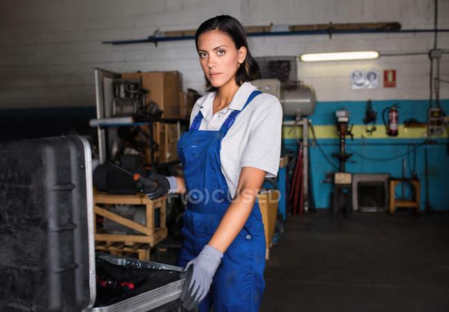 Retrato de mujer mecánico con un destornillador en la mano mirando a cámara - foto de stock
