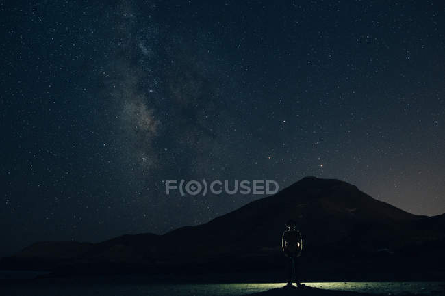 Silhouette of tourist against of starry sky above mountain silhouette at night — Stock Photo