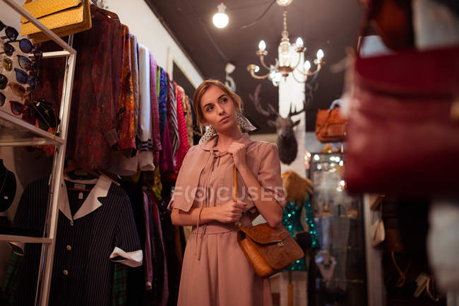 Young stylish girl in posing on background of clothing room. — Stock Photo