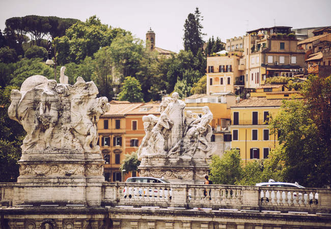 Sculptures ornées sur pont au-dessus de bâtiments communs façades sur toile de fond — Photo de stock