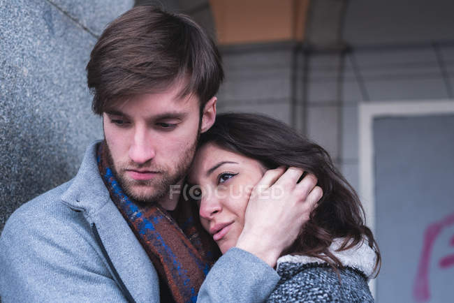Young couple hugging during dramatic scene in street. — Stock Photo