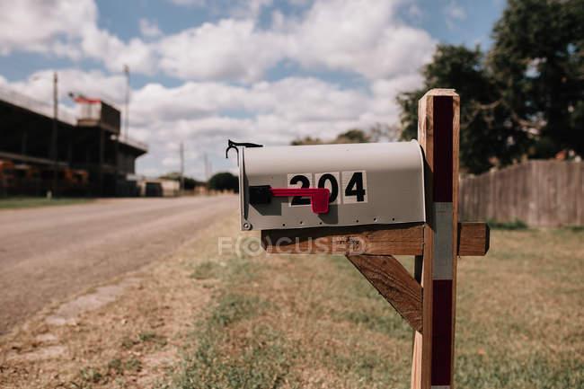 Chiusa cassetta postale di colore grigio chiaro sul ciglio della strada — Foto stock