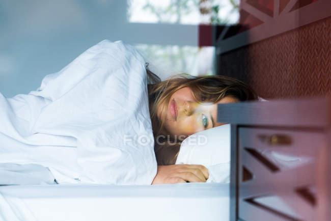 Bella ragazza bionda sdraiata sul letto e guardando la fotocamera — Foto stock