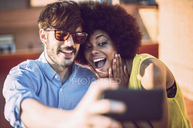 Cheerful young interracial couple taking selfie — Stock Photo