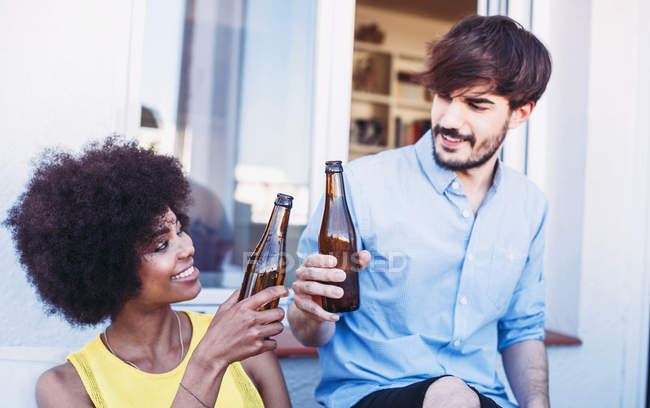 Happy multiracial friends clinking beers — Stock Photo