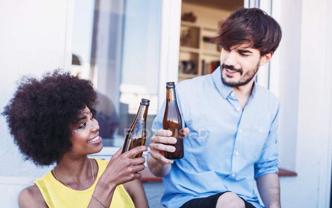 Heureux amis multiraciales tinter les bières — Photo de stock
