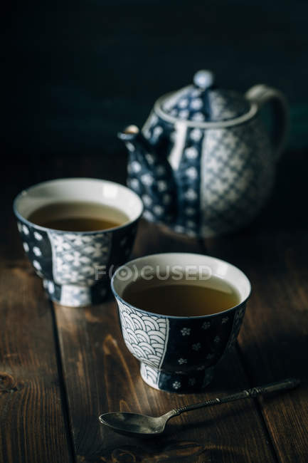 Two porcelain cups of hot tea by pot on wooden table. — Stock Photo