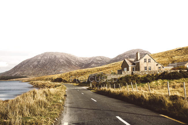 Ruhige Landschaft mit einsamer Straße und Haus vor dem Hintergrund der Berge. — Stockfoto