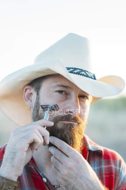 Портрет бородатого мужчины в ковбойской шляпе, бреющегося винтажной бритвой и смотрящего в камеру — стоковое фото