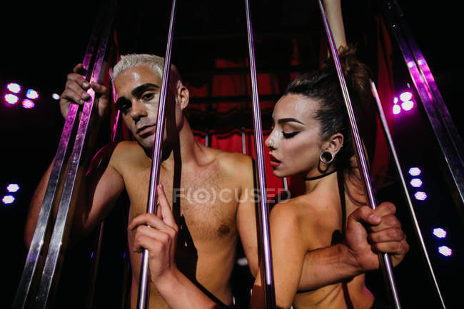 Topless couple posing behind metal poles — Stock Photo