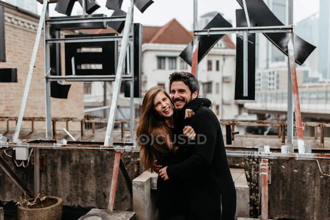 Усміхаючись пара в чорний одяг обіймаються на даху. — стокове фото