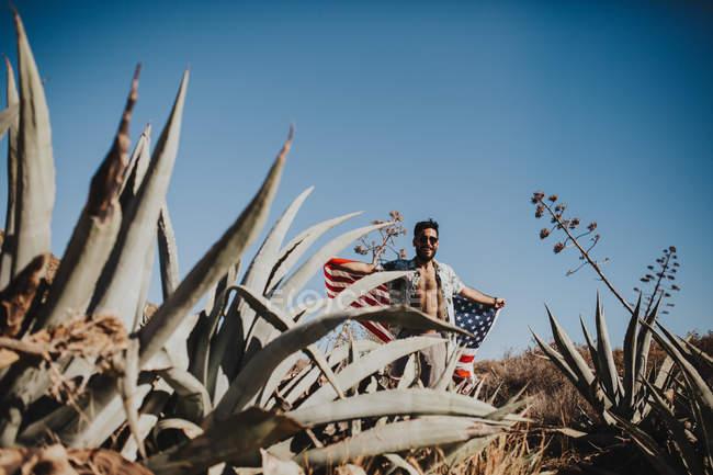 Glücklicher Mann mit Sonnenbrille, die amerikanische Flagge in ausgestreckten Armen gegen blauen Himmel hält — Stockfoto