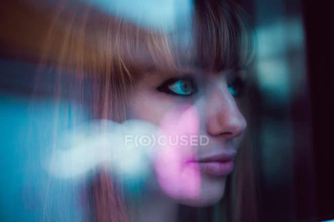 Portrait of redhead girl looking throush glassreflecting neon lights — Stock Photo