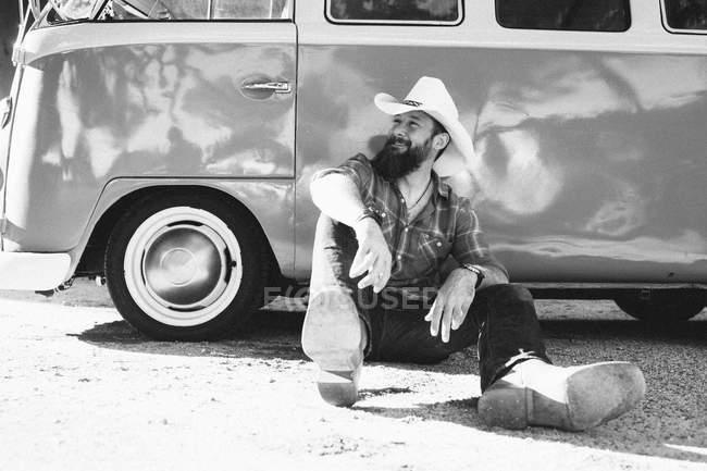Barbudo hombre en stetson sentado en el suelo y apoyado en van retro - foto de stock