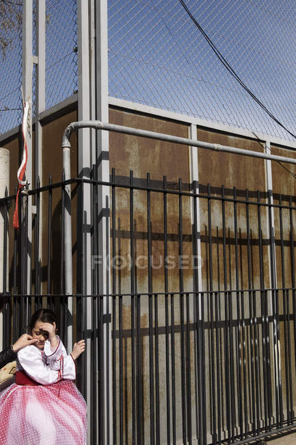 BARCELONA, SPAIN - 10 July, 2011: Crop hand consoling girl in costume while standing near metal fence. — Stock Photo