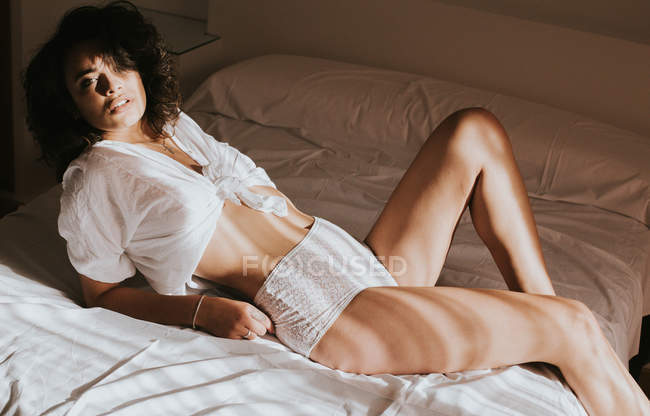 Seductive woman posing in lingerie on bed — Stock Photo
