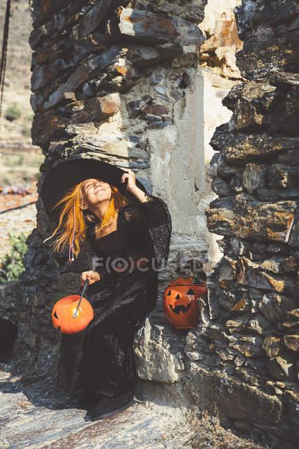 Девушка в шапке ведьмы позирует у каменной стены — стоковое фото