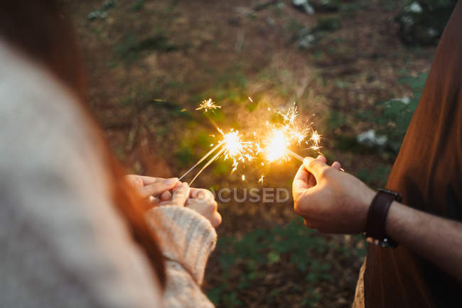 Hands with sparklers in woods — Stock Photo
