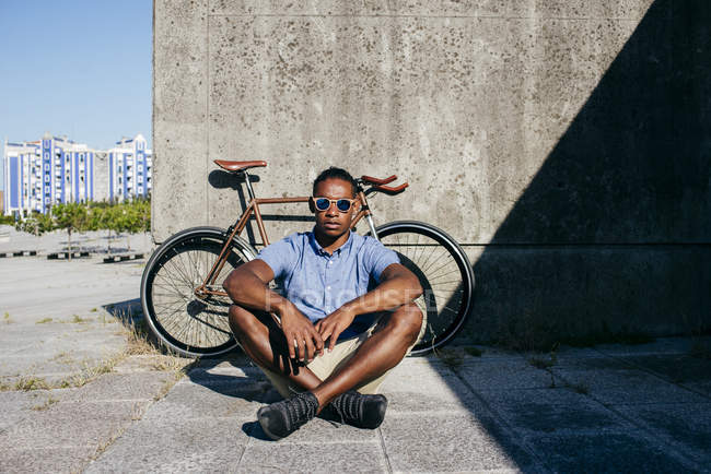 Man with sunglasses sitting near bicycle — Stock Photo