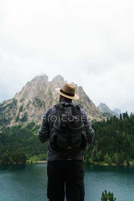 Tourist standing over mountains lake — Stock Photo