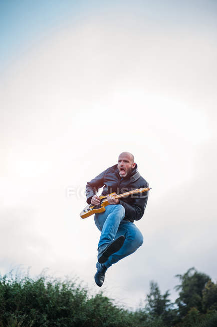 Expressive man with electric guitar in midair — Stock Photo