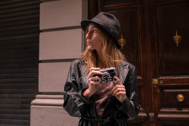 Young  woman in leather jacket and hat holding film camera and looking away — Stock Photo