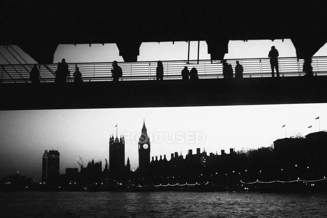 Vista de baixo ângulo de silhuetas em brdige olhando para passeios turísticos em Londres . — Fotografia de Stock