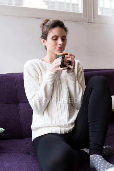 Портрет брюнетки, сидящей на тренере с ногами и наслаждающейся чашкой какао — стоковое фото