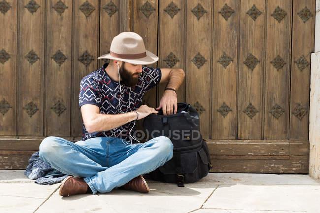 Hombre con barba en auriculares sentado en el suelo y buscar en la mochila - foto de stock