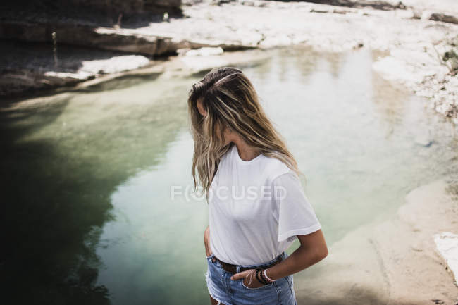 Blonde woman standing at lake shore — Stock Photo