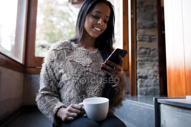 Ragazza sorridente con smartphone di navigazione tazza alla poltrona — Foto stock